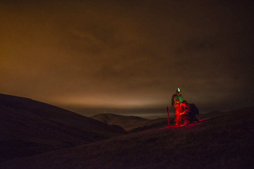 "Cpl. Brock O'Shaughnessy and Cpl. James Farran, U.S. Army Reserve Combat Engineer Soldiers with the 374th Engineer Company (Sapper), headquartered in Concord, Calif., find their first point during a night land navigation course through the hills and mountains of Camp San Luis Obispo Military Installation, Calif., July 15, during a two-week field exercise known as a Sapper Leader Course Prerequisite Training. The unit is grading its Soldiers on each event to determine which ones will earn a spot on a ""merit list"" to attend the Sapper Leader Course at Fort Leonard Wood, Mo."
