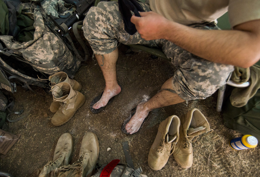 "A U.S. Army Reserve combat engineer Soldier from the 374th Engineer Company (Sapper), headquartered in Concord, Calif., powders his feet after a long day of land navigation July 15 as part of a two-week field exercise known as a Sapper Leader Course Prerequisite Training in July at Camp San Luis Obispo Military Installation, Calif. The unit is grading its Soldiers on each event to determine which ones will earn a spot on a ""merit list"" to attend the Sapper Leader Course at Fort Leonard Wood, Mo."