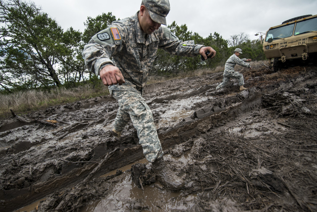 Sgt. Robert Gonzales, maintenance squad leader for the 277th Engineer Company (Horizontal), of San Antonio, Texas, jumps over a mud trail after helping recover a vehicle that had been stuck from another unit at Camp Bullis, Texas, March 22. (U.S. Army photo by Sgt. 1st Class Michel Sauret)