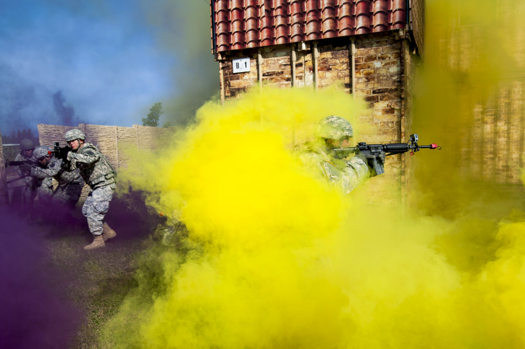 A team of Soldiers belonging to the 450th Engineer Company, the 350th Eng. Co., and the 374th Eng. Co., moves through concealing smoke to enter and clears a building as one of the evaluated exercises for Sapper Stakes at Fort McCoy, Wis., May 6. Sapper Stakes is a combined competition hosted by the 416th Theater Engineer Command and the 412th TEC to determine the best combat engineer team in the Army Reserve. (U.S. Army photo by Sgt. 1st Class Michel Sauret)
